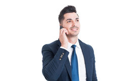 Confident young businessman calling on smartphone and smiling Royalty Free Stock Images