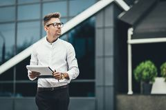 Confident young businessman dressed in stylish corporate suit holding financial documents in hand and strolling in urban royalty free stock photo
