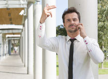 Confident young businessman gesturing while using mobile phone outside office Stock Photos