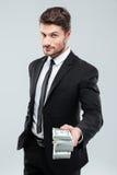 Confident young businessman giving money to you Stock Photos