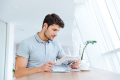 Confident young businessman reading newspaper and drinking coffee Stock Photography