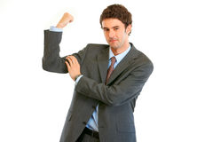 Confident young businessman showing his  muscles Stock Photo