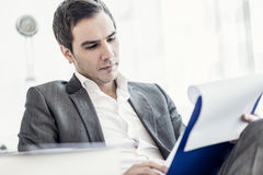 Confident young businessman sitting at his desk reading a docume Stock Images