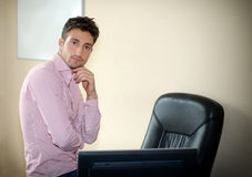 Confident young businessman sitting on office desk Royalty Free Stock Photos