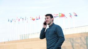 Communication concept. Confident young businessman standing outdoors over different countries flags background talking on mobile phone. International stock video
