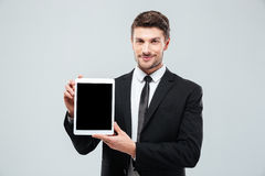 Confident young businessman standing and showing blank screen tablet Royalty Free Stock Photo