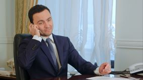 Confident young businessman takes a call in a modern office royalty free stock photos