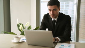 Confident young businessman using laptop at office, looking at camera. Confident cheerful businessman in suit using laptop sitting at workplace, working on stock video