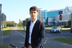 Confident young businessman walking with bicycle on the street in town. Royalty Free Stock Photos