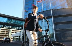 Confident young businessman walking with bicycle on the street in town. Stock Photos
