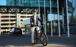 Confident young businessman walking with bicycle on the street in town. Royalty Free Stock Image