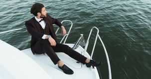 Confident young businessman on a yacht or boat against a sea. He is pleased with the success in his business and his stock footage