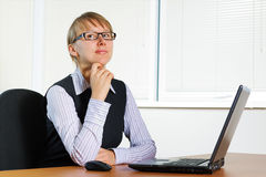 Confident young businesswoman. Young businesswoman working on the laptop at office Royalty Free Stock Image