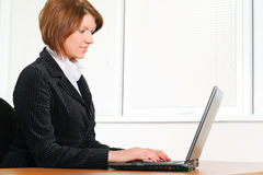 Confident young businesswoman. Young businesswoman working on the laptop at office Royalty Free Stock Photography