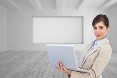 Confident young businesswoman with laptop. Composite image of confident young businesswoman with laptop Royalty Free Stock Photography