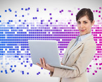 Confident young businesswoman with laptop. Composite image of confident young businesswoman with laptop Stock Photo