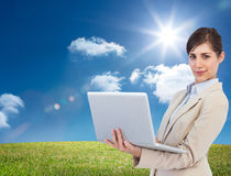 Confident young businesswoman with laptop. Composite image of confident young businesswoman with laptop Stock Photography