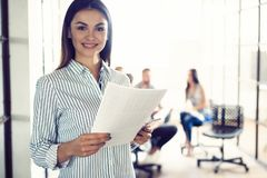 Confident young businesswoman standing with documents in a modern office with colleagues working in the background. royalty free stock photography