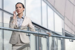 Confident young businesswoman using cell phone at office balcony Stock Photo