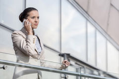 Confident young businesswoman using smart phone at office railing Royalty Free Stock Photo