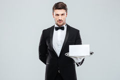 Confident young butler holding blank card on tray. Confident young butler in tuxedo holding blank card on tray stock photography