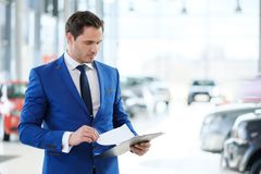 Confident young car dealer standing in  showroom. Stock Photo