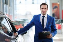 Confident young car dealer standing in  showroom. Stock Photography