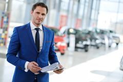 Confident young car dealer standing in  showroom. Royalty Free Stock Images