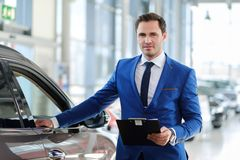 Confident young car dealer standing in  showroom. Royalty Free Stock Image