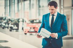Confident young car dealer standing in  showroom. Royalty Free Stock Photos