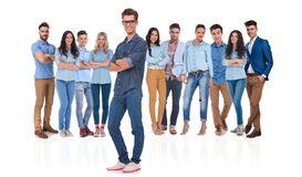 Confident young casual group with their leader standing in front. Of them with hands crossed on white background stock images