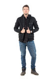 Confident young casual male in hooded black winter jacket and jeans Royalty Free Stock Photo