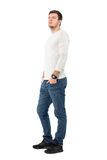 Confident young casual man in jeans and gray shirt looking up. Full body length portrait isolated over white studio background Royalty Free Stock Image