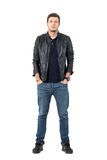 Confident young casual man in leather jacket and jeans with hands in pockets. Stock Image