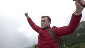 Confident young climber with open arms celebrating the achievement on top of mountain after a trekking hike  -. Confident young climber with open arms stock video