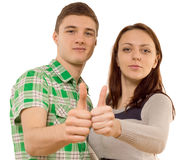 Confident young couple showing thumbs up, on white. Caucasian confident young couple standing side by side, wearing casual clothes while smiling discreetly Royalty Free Stock Photos