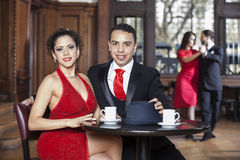 Confident Young Couple Sitting At Table While Tango Partners Dan. Portrait of confident young couple sitting at table while tango partners dancing in restaurant Royalty Free Stock Photos