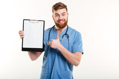 Confident young doctor holding clipboard and giving thumb up Royalty Free Stock Image