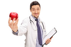 Confident young doctor offering an apple Royalty Free Stock Images