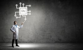 Doctor and processor icon. Confident and young doctor in white medical uniform standing against dark gray wall on background and interracting with glowing royalty free stock photo