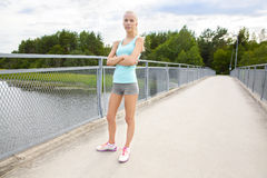 Confident young female runner stands at bridge Stock Photos