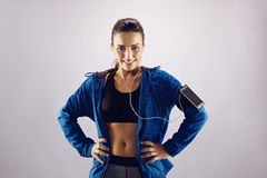 Confident young female in sports gear. Portrait of happy young female athlete with her hands on hips standing on grey background. Smiling caucasian woman in Royalty Free Stock Photo