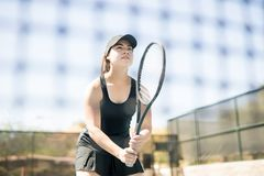 Confident athlete playing tennis on court. Confident young female tennis player with racket standing behind the net on court Stock Images