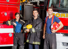 Confident Young Firefighters Standing Against. Portrait of confident young firefighters standing against trucks at fire station Stock Image