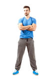 Confident young fit male with folded hands looking away. Full body length isolated over white background Royalty Free Stock Photos