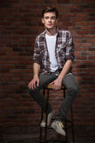 Confident young guy sitting on bar chair Royalty Free Stock Image