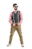 Confident young hipster holding suspenders looking away Stock Photo