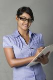 Confident Young Indian woman write on clipboard Stock Photo