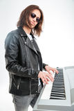 Confident young keyboardist in sunglasses standing and playing on synthesizer Royalty Free Stock Photography