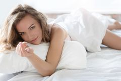 Confident young lady locating on bedding Royalty Free Stock Photography